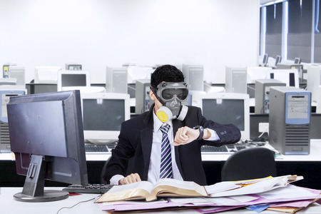 office environment: Businessman working in office with a gas mask and looking at his watch