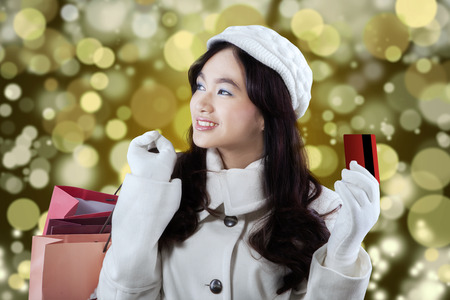 Portrait of young girl in winter coat holding credit card and shopping bags with a light glitter background photo