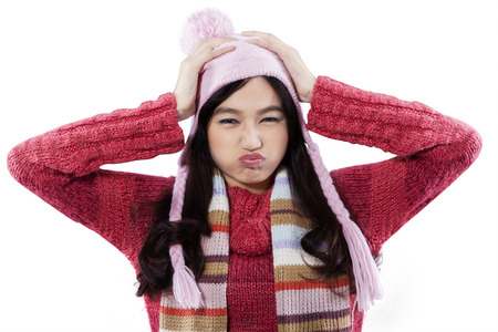 cranky: Cranky expression of young girl wearing knitted clothes and hat, isolated on white background