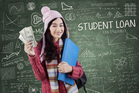 financial education: Young female student wearing winter wear and standing in the class while holding money dollars Stock Photo