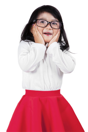 kids dress: Young little girl with shocked expression and wearing glasses in the studio, isolated on white