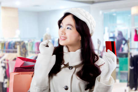 Gorgeous girl in winter clothes holding a credit card and shopping bags in the shopping center photo