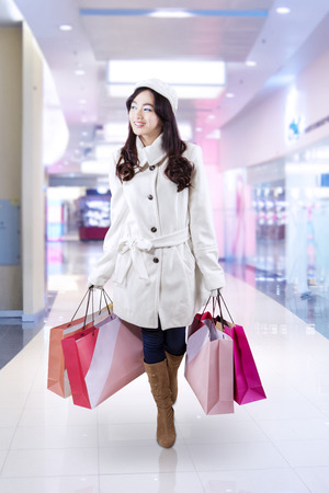 Lovely girl wearing winter clothing, walking in shopping center while carrying shopping bags