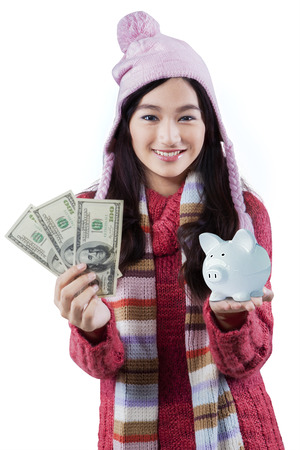 indian currency: Beautiful girl in winter clothes holding a piggybank and dollar bills, isolated on white background Stock Photo