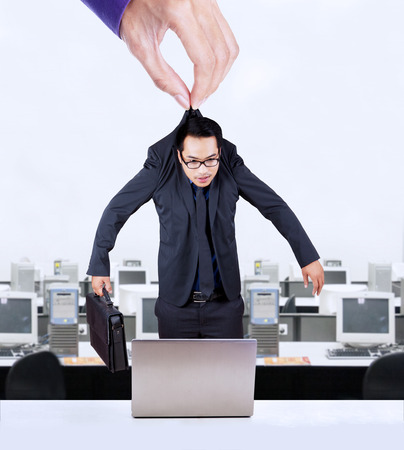 exploitation: Businessman hanging on a hand and put in an office to work, symbolizing worker exploitation