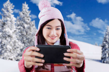Beautiful young girl in warm clothes and hat, taking self picture with a smartphone near snowy mountain photo