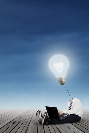 Little boy with lamp head using laptop photo