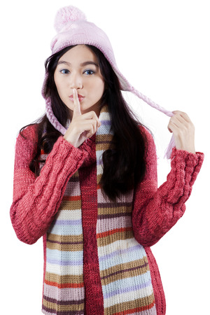 Portrait of beauitful young woman in winter clothes putting finger on mouth, isolated on white photo