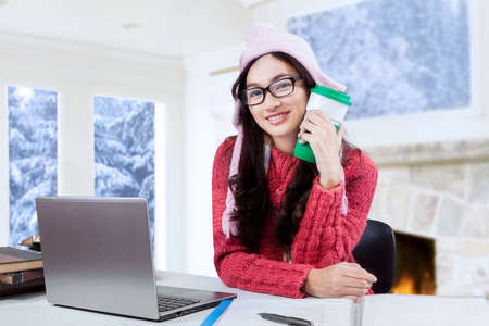 warm drink: Young girl smiling at the camera while holding a cup of warm drink and studying on the table at home