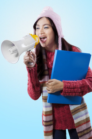 bawl: Young female student in winter clothes, holding a folder and screaming with a megaphone
