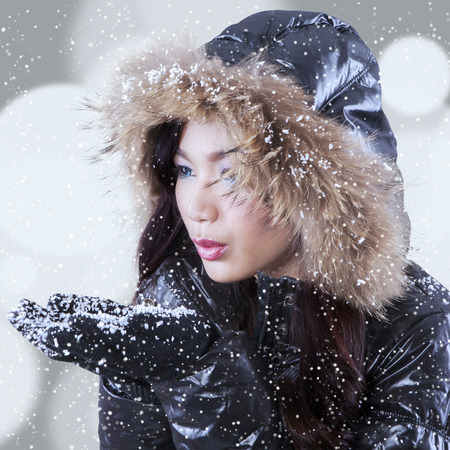 Young girl blowing snow on her palms in the snowy day with light glitter background photo