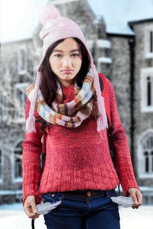 bolsa dinero: Alumna tristes que tienen problema financiero y que muestra los bolsillos vacíos cerca del edificio de la escuela