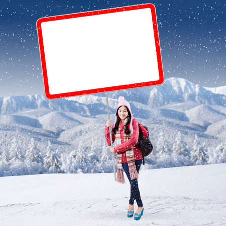 Cheerful female student in winter clothes holding blank board at snowy mountain photo