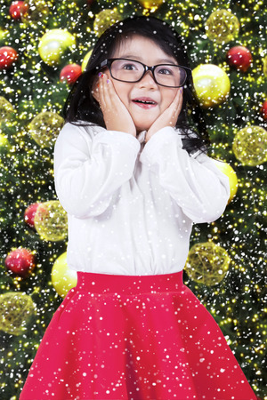 Sweet expression of little girl standing near christmas tree with full christmas ornaments photo