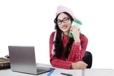 Teenage girl wearing a winter knitted clothes, doing schoolwork and smiling at the camera while holding a cup of warm coffee photo
