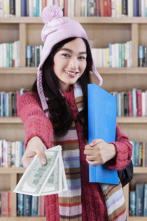 education loan: Female student with warm clothes in the library, offering money dollars for student loan Stock Photo