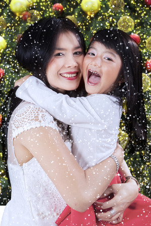 Cute little girl embrace her mother while laughing happily with christmas tree background photo