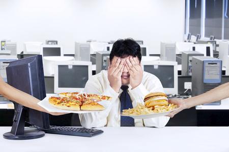 comida chatarra: Hombre de negocios con sobrepeso tratar de vida saludable y evitar la tentación de la comida rápida Foto de archivo