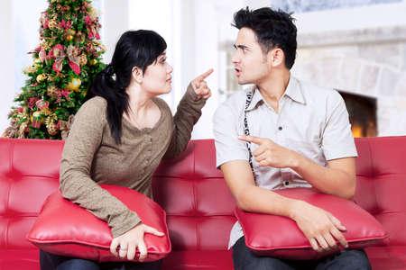 arbol de problemas: Retrato de pareja pelea, señalando, y culparse unos a otros en su casa en el día de Navidad Foto de archivo