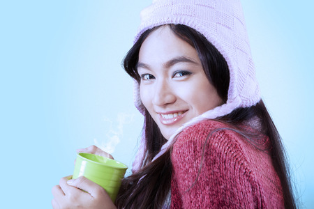 Portrait of attractive hispanic girl wearing warm clothes and looking at the camera while holding a coffee cup photo