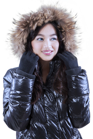 Portrait of attractive girl wearing winter clothes with fur hood in studio, isolated on white photo