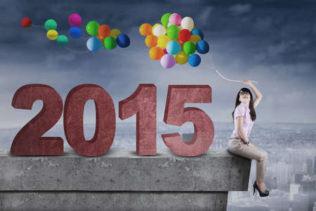 Young woman sitting on rooftop with number 2015 and holds colorful balloons, symbolizing smart woman with creative idea for future 2015 photo