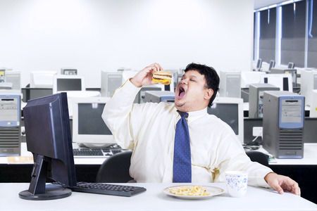 diet food: Young businessman with fat body working in the office while eating junk food
