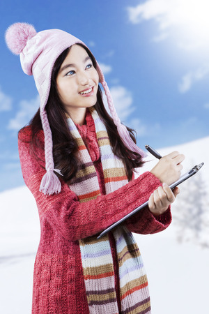observe: Beautiful girl wearing winter clothes, standing outdoors while observe something and writes the report on clipboard