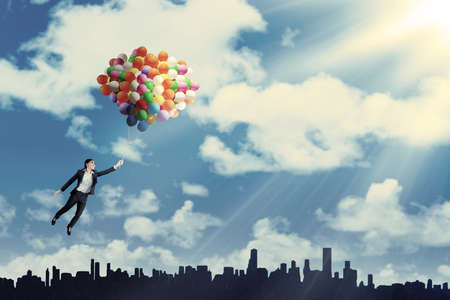 aspirations ideas: Businesswoman flying with balloons over cityscape to get success Stock Photo