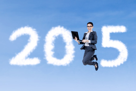year increase: Asian businesswoman jumping on the sky with laptop computer and forming number 2015