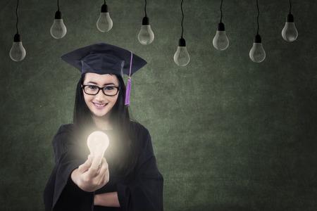 Beautiful Asian female graduate giving lit bulb under lamps