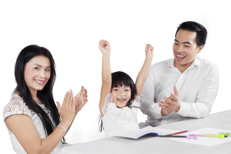 Portrait of two parents giving applause to her daughter after finishing her homework photo