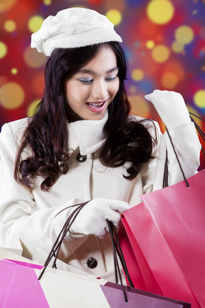 Portrait of joyful wearing winter fashion and looking at the shopping bags, shot against bokeh background photo