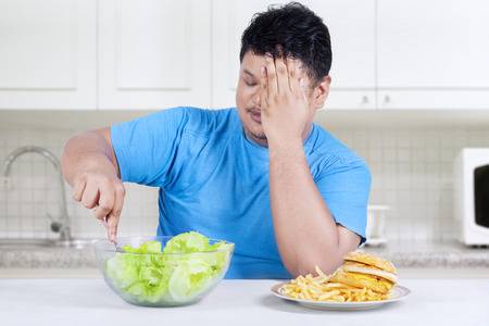 reject: Starting healthy eating; overweight person rejects junk food