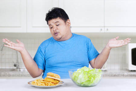 Overweight person doubt to choose junk food or healthy food Stock Photo