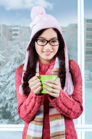 Portrait of young teenage girl wearing winter fashion and smiling at the camera near the window photo