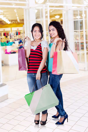 carrying girl: Portrait of beautiful girls standing in the shopping center while holding shopping bags and smiling at the camera Stock Photo