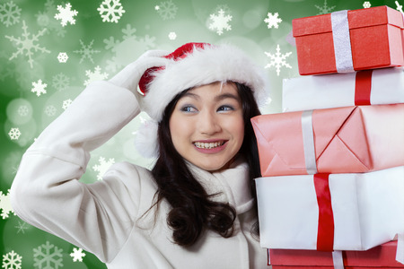 Portrait of happy girl scratching her head while holding christmas gifts with winter background photo
