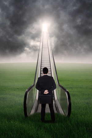 Businessman is walking up the escalator from the green field photo