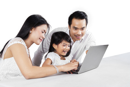 Portrait of happy family using laptop computer together on the table, isolated on white background Stock Photo