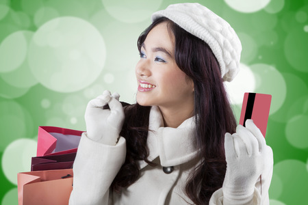 Portrait of young woman wearing winter coat, smiling happy while carrying shopping bags and holding credit card photo