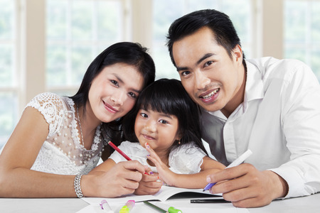 schoolwork: Portrait of happy family doing homework together at home and smiling at the camera