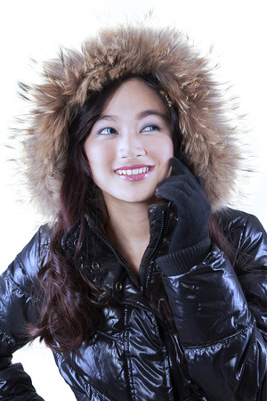 Beautiful smile of young girl wearing fur jacket in studio, isolated on white background photo