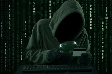scammer: Internet Theft - a man wearing a balaclava looking at credit card code using magnifying glass Stock Photo