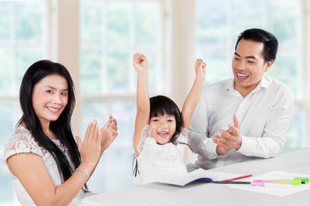 Cheerful girl finishing her homework and getting applause from her parents photo