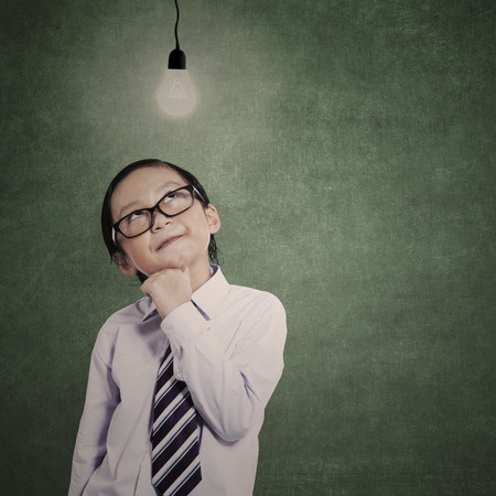 lit: Little businessman under lit bulb in classroom