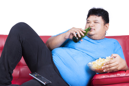 overweight man: Overweight man sitting lazy on sofa while drinking beer and eat snack