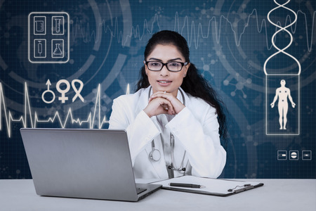 Portrait of female indian doctor with curly hair looking at the camera in front of medical background photo