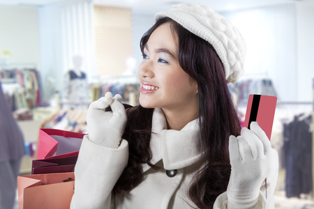Portrait of a teenage girl shopping in the mall using a credit card and wearing winter coat photo