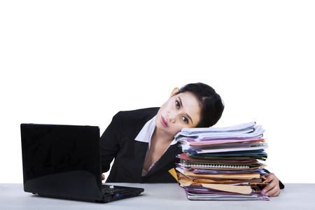 Depressed young businesswoman with a pile of documents photo